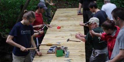 Volunteers hammering wooden bridge