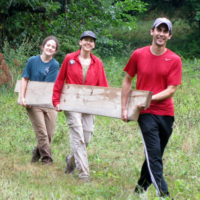 Three Smiling Volunteers Carring Long Board