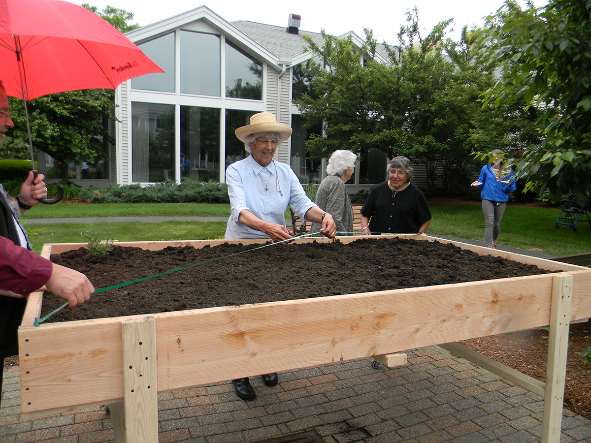 Seniors cutting ribbon on new raised bed garden