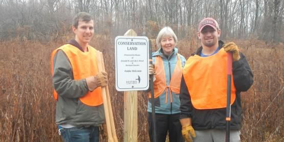 Volunteers stand with new sign