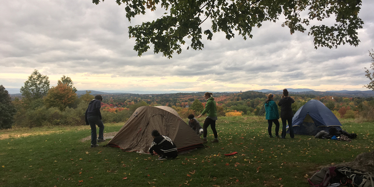 Highschool Students Putting Up Tents In Open Field