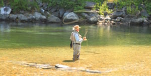 man fly fishing in clear stream