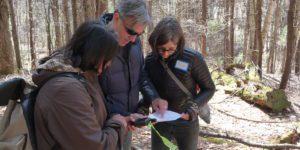 volunteers in woods with GPS unit