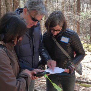 Volunteers In Woods With GPS Unit
