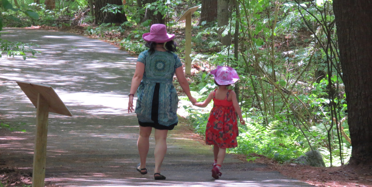 Mom and girl on story walk path