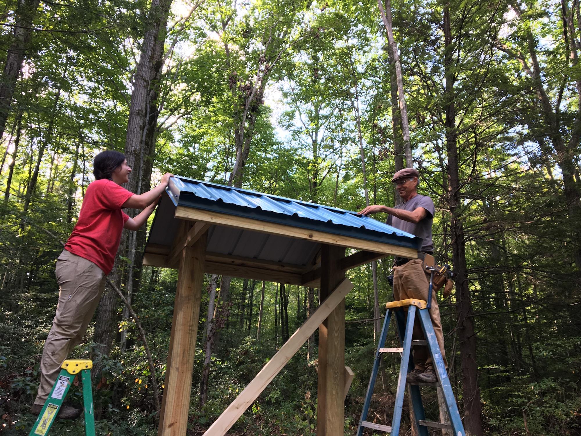 Volunteers on ladders building kiosk