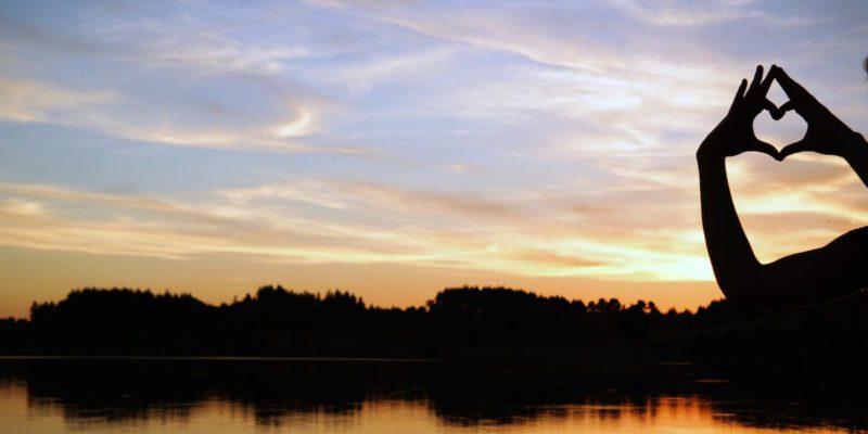 Hands Making Heart Over Sunset