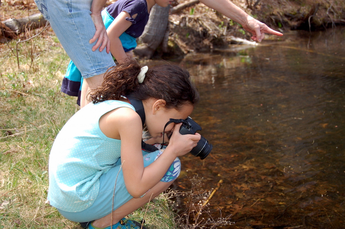 Girl Taking Photo Of Stream