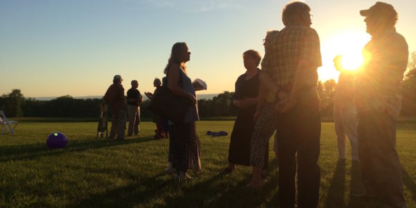 People At Sunset In A Field