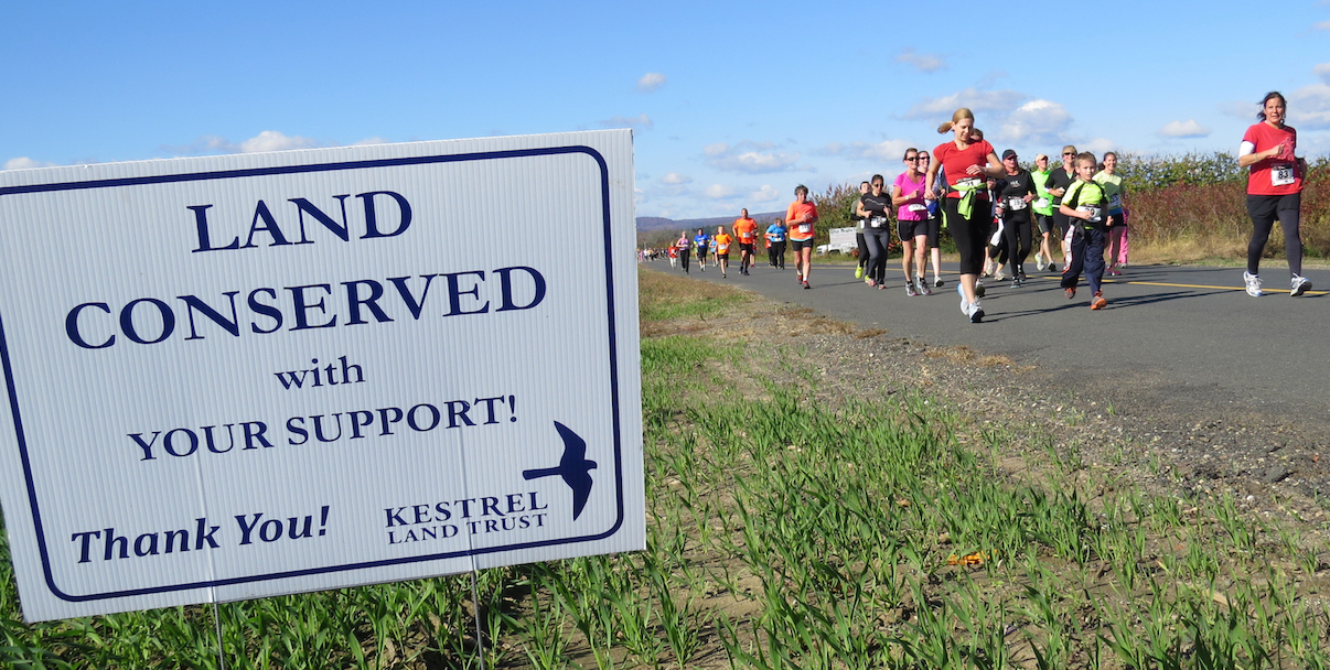 Runners With Land Conserved Sign